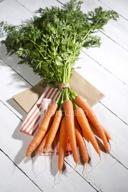 Ramo de zanahorias orgánicas sobre tela sobre mesa de madera blanca - foto de stock