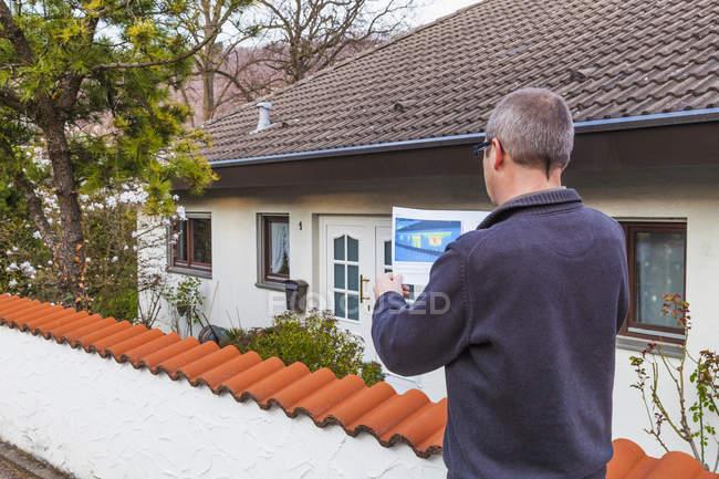 Человек, держащий термографию здания на открытом воздухе — стоковое фото