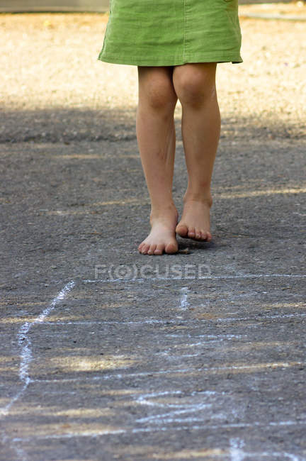 Little barefoot girl playing hopscotch — Stock Photo