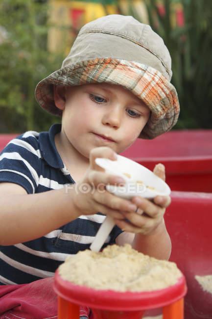 Портрет маленького мальчика, играющего в песочнице — стоковое фото