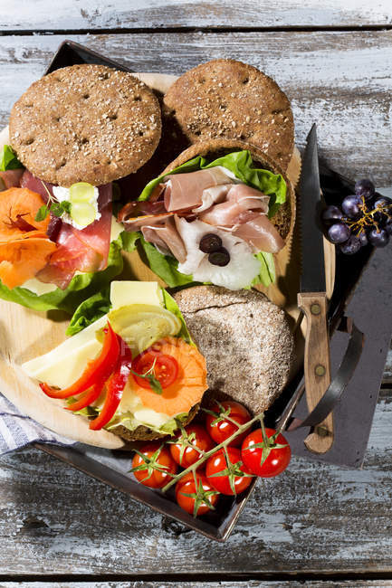 Organic rye bun with ham, cheese, grapes and tomatoes — Stock Photo