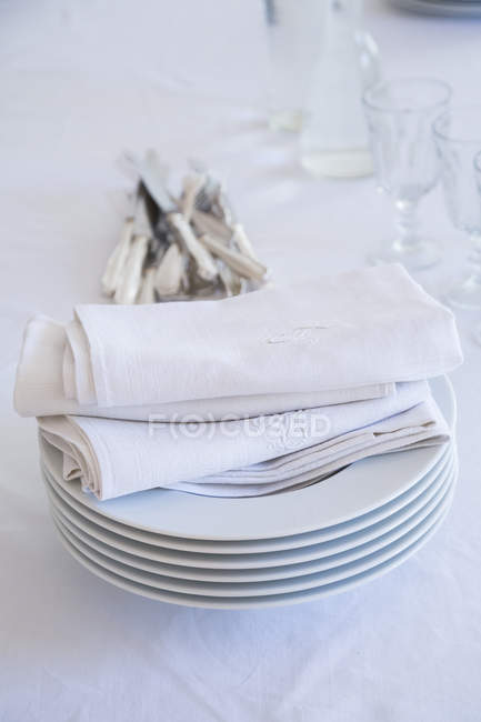 Closeup of glasses, stack of plates with cloth napkins and silver cutlery on white table cloth — Stock Photo