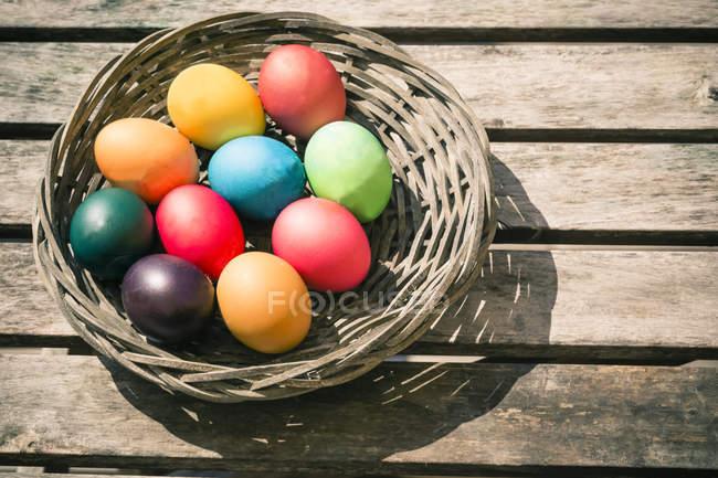 Elevada visão da cesta com colorido Páscoa ovos na mesa de madeira — Fotografia de Stock