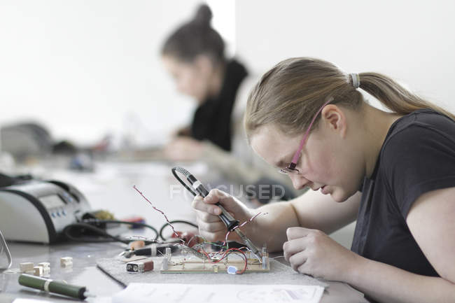 Two young women working on optical sensor in electronic workshop — Stock Photo