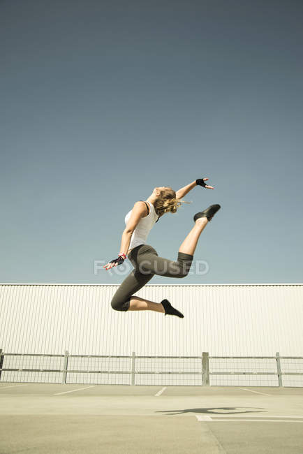 Young woman jumping mid-air on parking level — Stock Photo
