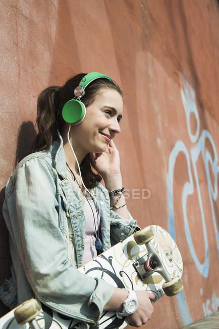 Adolescente sorridente con musica di udienza di skateboard — Foto stock