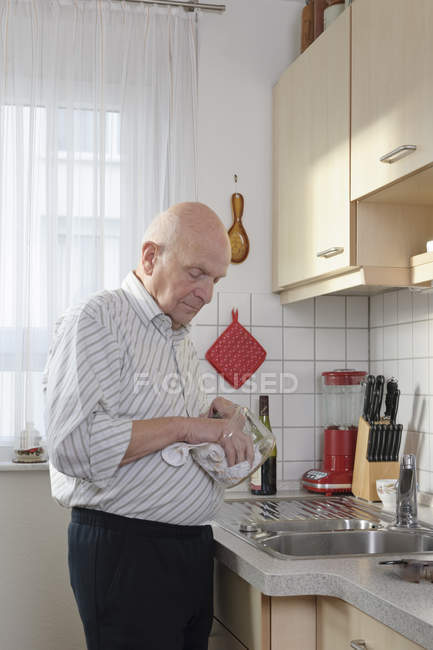 Old man drying coffee pot in kitchen — Stock Photo