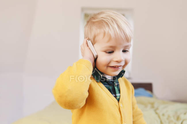 Portrait of smiling toddler telephoning with smartphone — Stock Photo