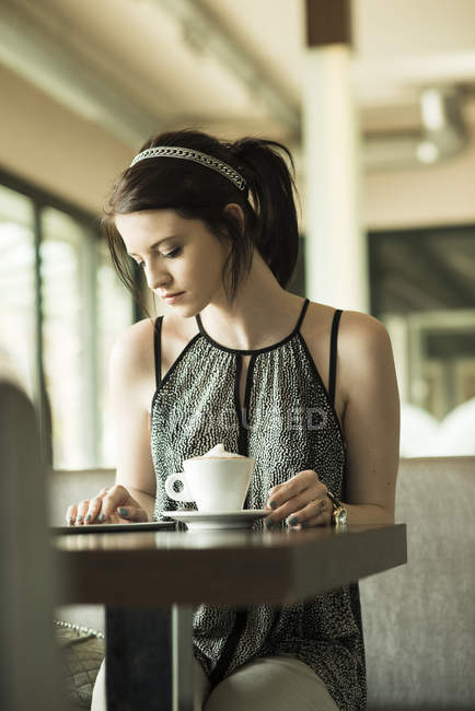 Portrait of young woman using tablet computer at cafe — Stock Photo