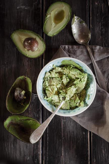 Миска дроблена авокадо, кухонне рушник, ложка і нарізаний і видовбаних половинок два авокадо на дерев'яні таблиці — стокове фото
