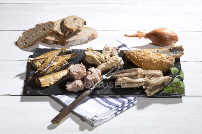 Varietà di pesce marinato e marinato su ardesia su tavola di legno bianca con pane — Foto stock