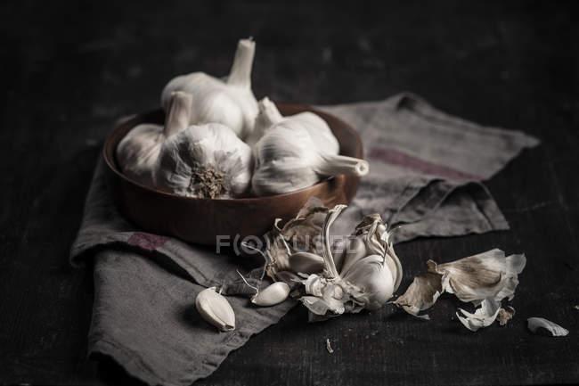 Dientes de ajo y bulbos sobre fondo oscuro con tela - foto de stock