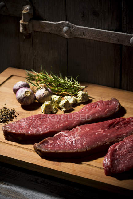 Beefsteak, garlic, rosemary, herb butter and pepper on chopping board — Stock Photo