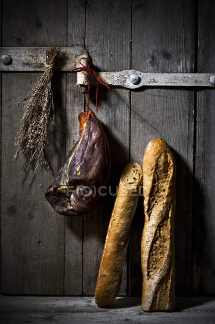 Smoked ham and onion baguette on wooden door — Stock Photo