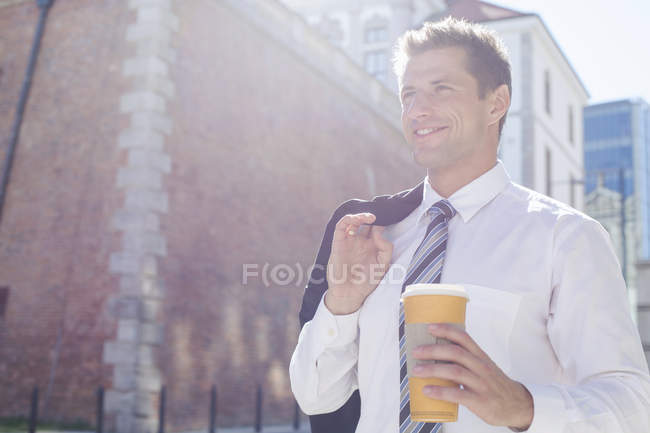 Businessman holding disposable cup — Stock Photo