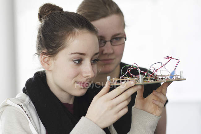 Two young women holding component of optical sensor in electronic workshop — Stock Photo