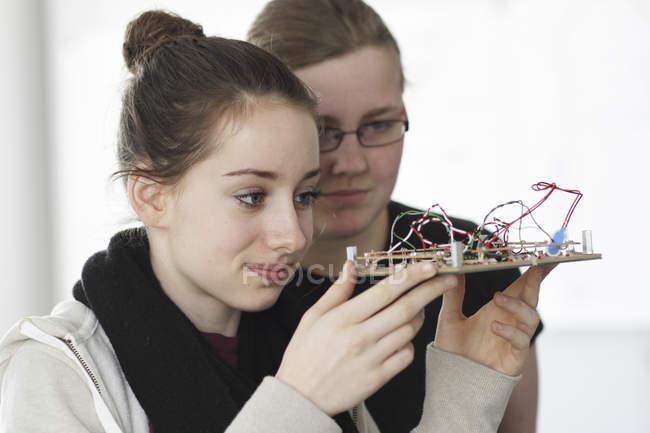 Deux jeunes femmes tenant un composant de capteur optique dans un atelier électronique — Photo de stock