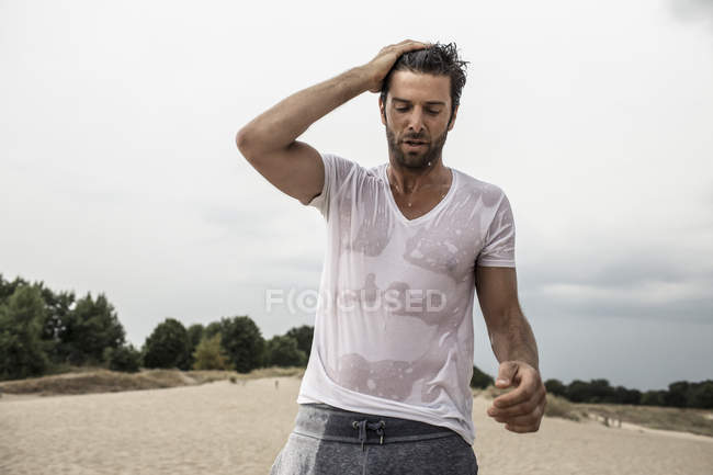 Portrait of stylish man wearing wet t-shirt touching hair — Stock Photo