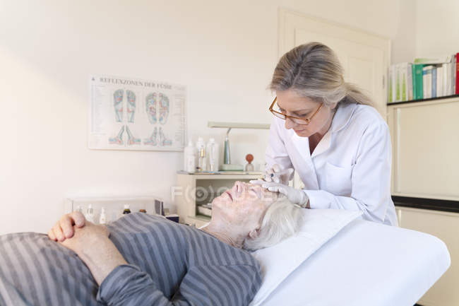 Female alternative practitioner giving senior woman injection acupuncture — Stock Photo