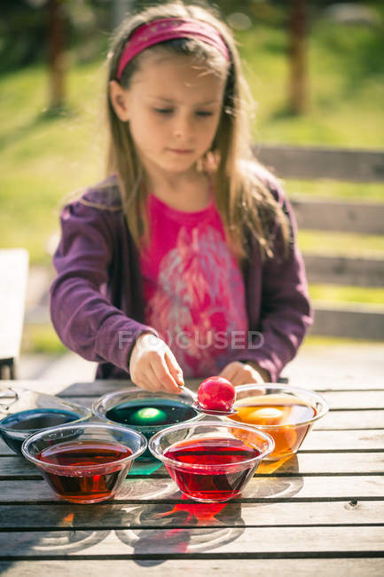 Girl dyeing Easter eggs at park — Stock Photo