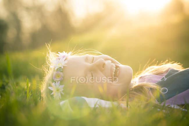 Портрет сміється дівчинка, лежачи на луг носіння квіти — стокове фото