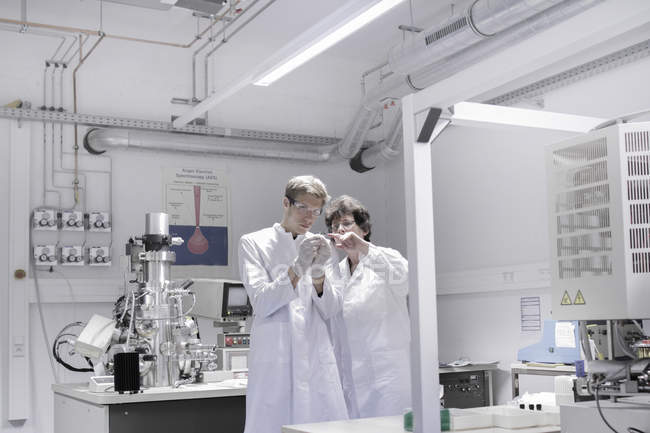 Two scientists standing in analytical laboratory with scanning electron microscope — Stock Photo
