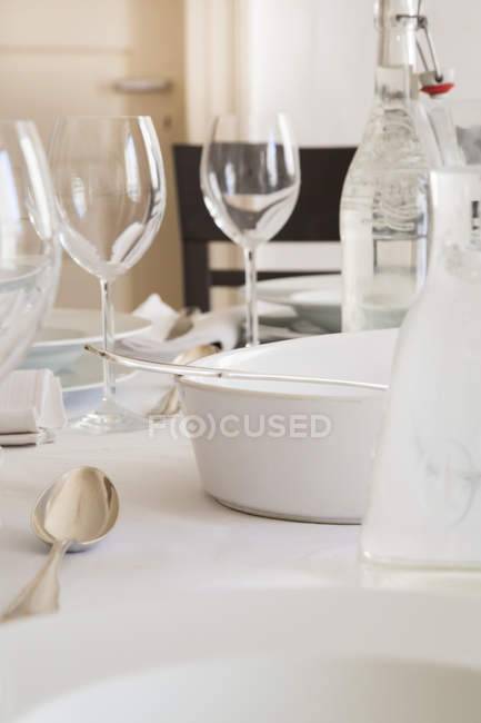 Mesa festiva con copas de vino, cubiertos de plata y botella de agua - foto de stock