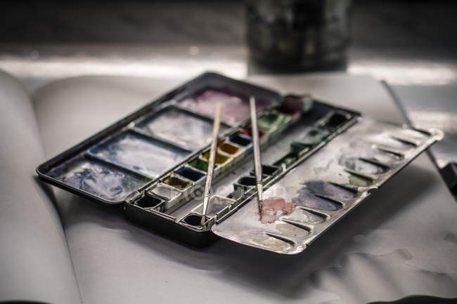 Used water colour paint box and two brushes on sketchbook — Stock Photo