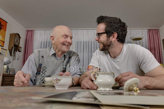Grandfather and grandson drinking coffee at home — Stock Photo
