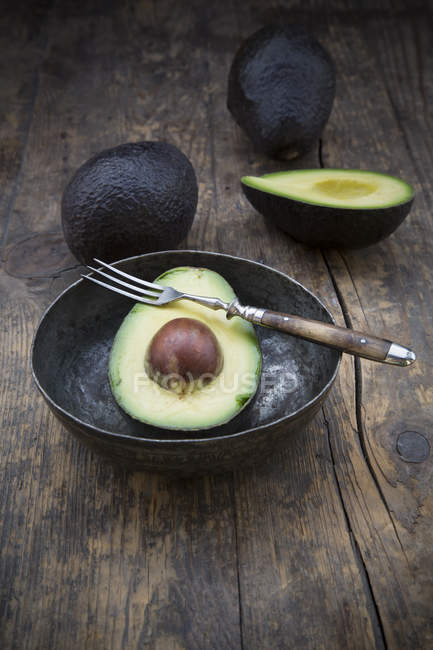 Halbierte und ganze Avocado mit Schüssel und Gabel auf Holztisch — Stockfoto