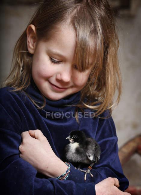 Портрет маленькой девочки, держащей цыпленка — стоковое фото