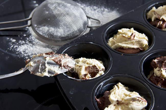 Masa cruda muffin en la bandeja de muffins, cuchara y colador, primer plano - foto de stock