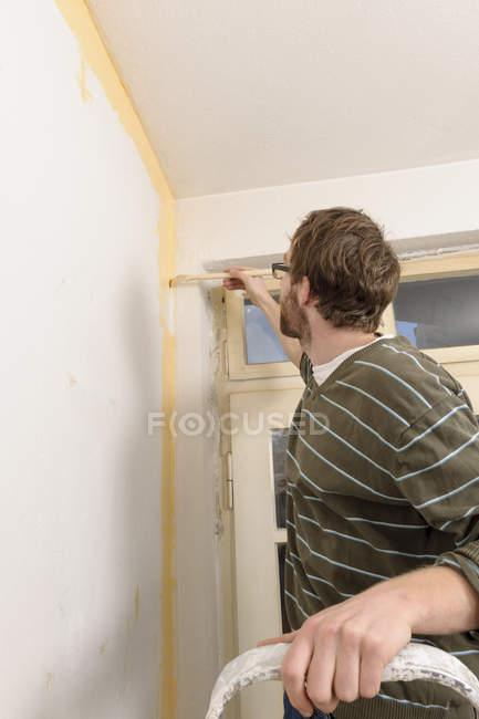 Молода людина реставрації подушок нову квартиру — стокове фото