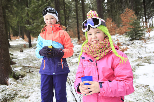 Two teenage girls wearing colourful winter clothes standing in nature — Stock Photo