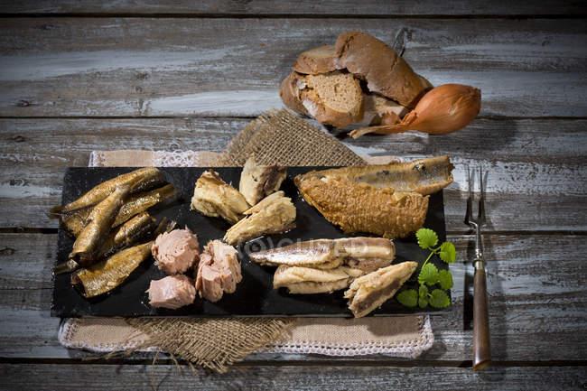 Разнообразие соленые и маринованные рыб на шифер с хлеба на потертом древесины — стоковое фото