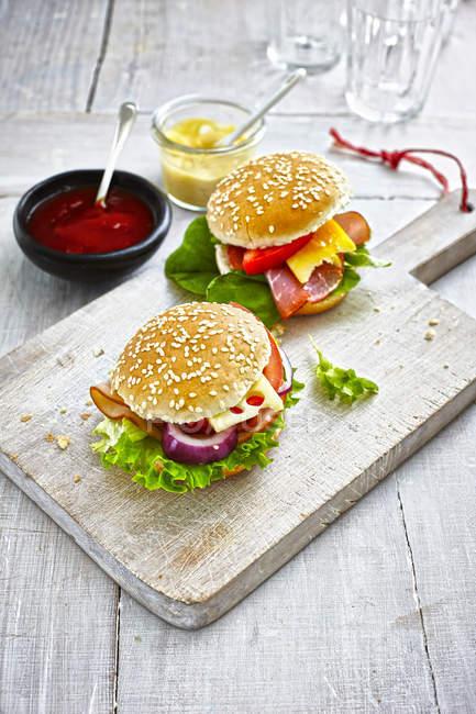 Dos preparan hamburguesas, mostaza y ketchup en el suelo de madera - foto de stock