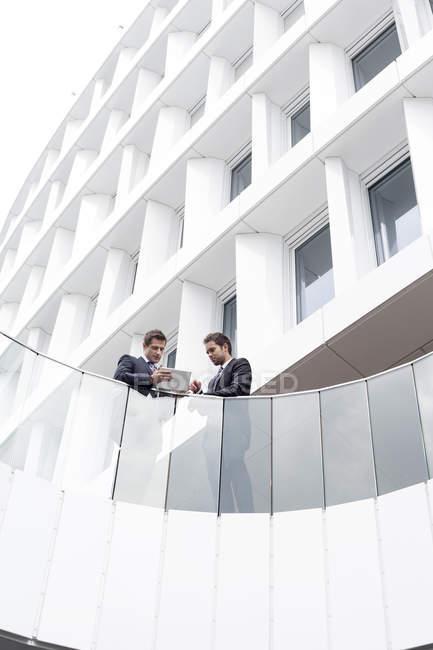 Deux hommes d'affaires avec tablette devant l'hôtel — Photo de stock