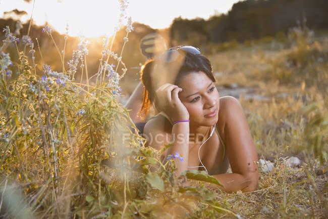 Девочка-подросток лежит на лугу с наушниками — стоковое фото