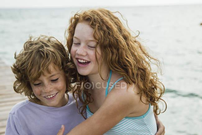 Дівчинка і хлопчик обіймати на море — стокове фото