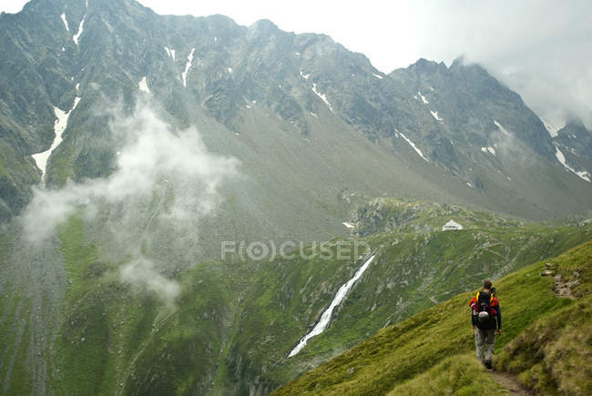 Austria, Tirol, Mid adult man walking to alpine hut — Stock Photo