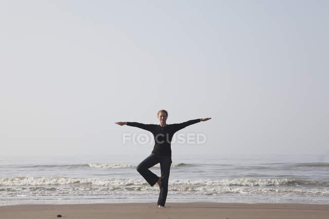 Belgique, Jeune femme debout dans la pose d'arbre à la mer du Nord — Photo de stock