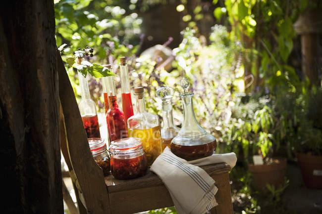 Diverses huiles à base de plantes sur chaise dans le jardin rural — Photo de stock