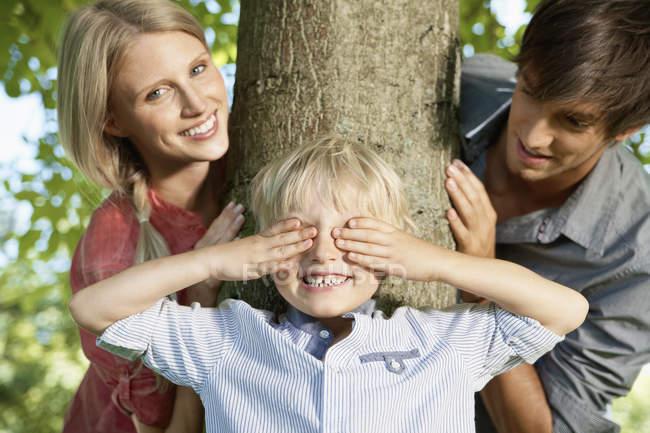 Menino brincando de esconde e procura com os pais — Fotografia de Stock