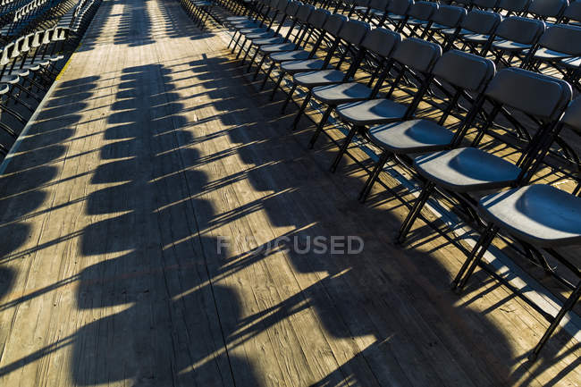 Empty chairs before event with shadows in sunlight — Stock Photo