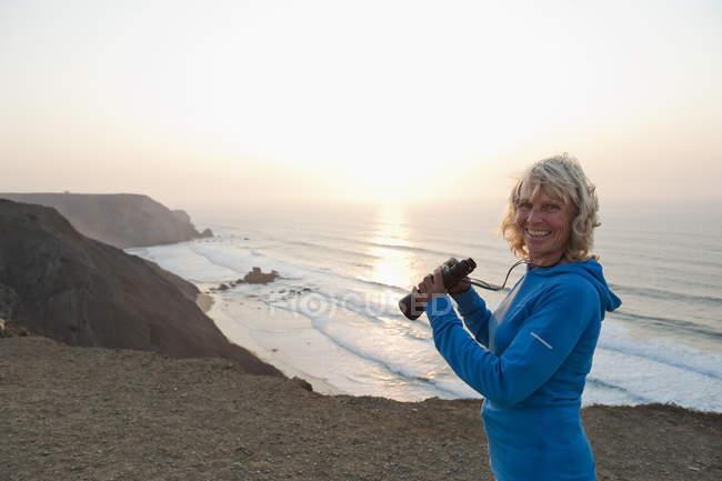 Португалия, Алгарве, Сагреш, пожилая женщина с биноклем на пляже — стоковое фото