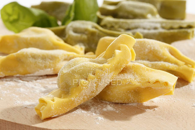 Candy shape pasta with flour and basil leaf on chopping board — Stock Photo
