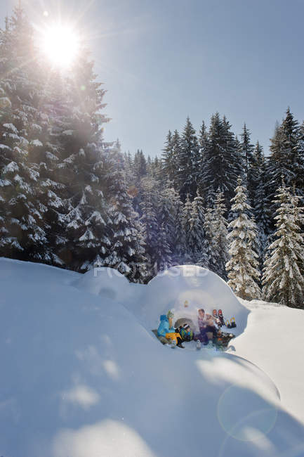 Сім'я, відпочиваючи біля сніг igloo у Зальцбурзі, Австрія — стокове фото