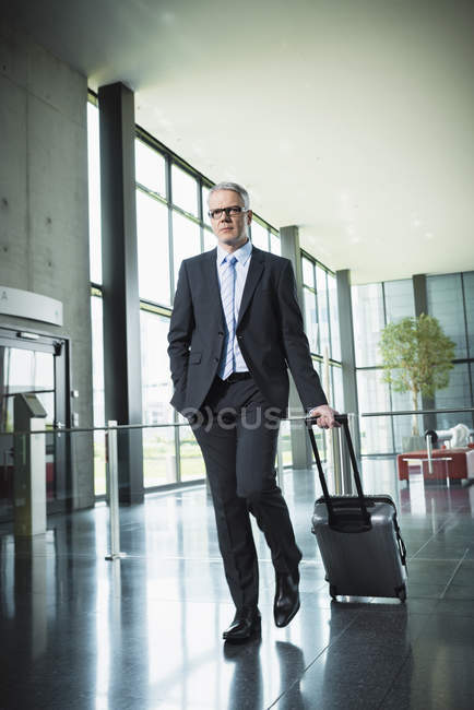 Businessman pulling luggage in office building — Stock Photo