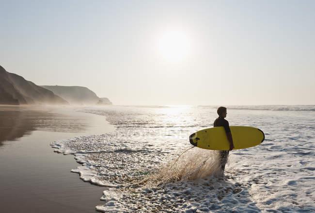 Surfista na praia ao pôr do sol cênico — Fotografia de Stock