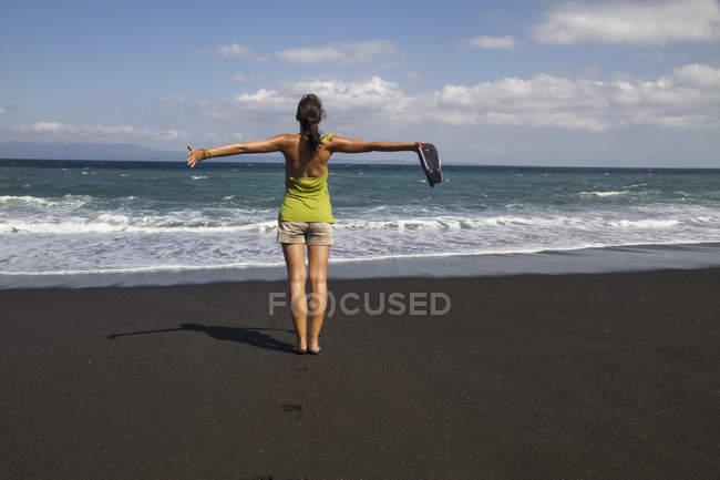 Молодая женщина, стоя на черном песке — стоковое фото